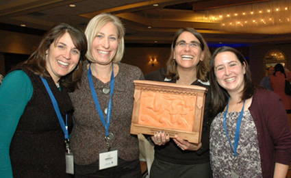 Herzl Camp staff and volunteers proudly display the Impact in Technology Award at the Grinspoon Institute's ninth annual Camping Conference. Pictured above are (l to r): Lauren Kaplan, immediate past president; Sue Roether, president; Anne Hope, camp director; and Drea Lear, program coordinator. (Photo: Courtesy of Herzl Camp)